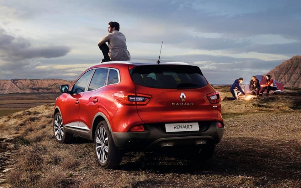 Rød Renault Kadjar parkert med mann på taket foran tre mennesker som tenner bål på et fjell
