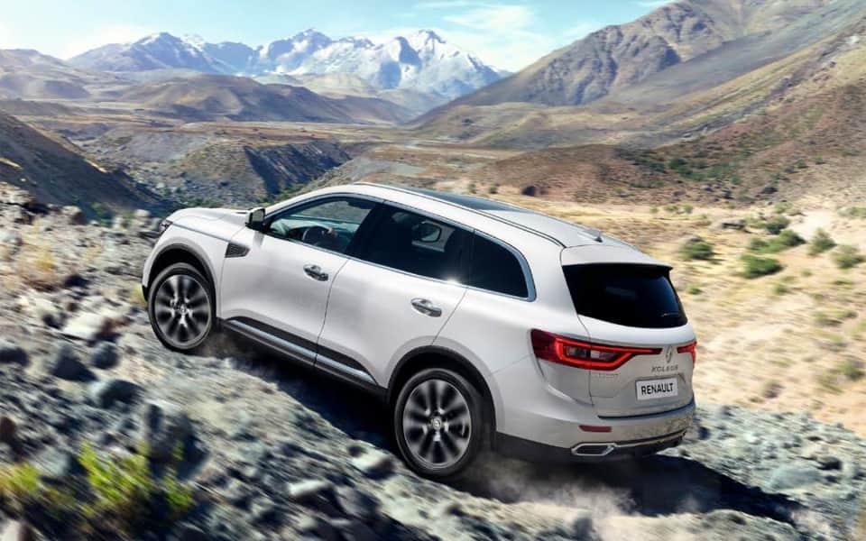 Hvit Renault Koleos kjører off road i fjellene