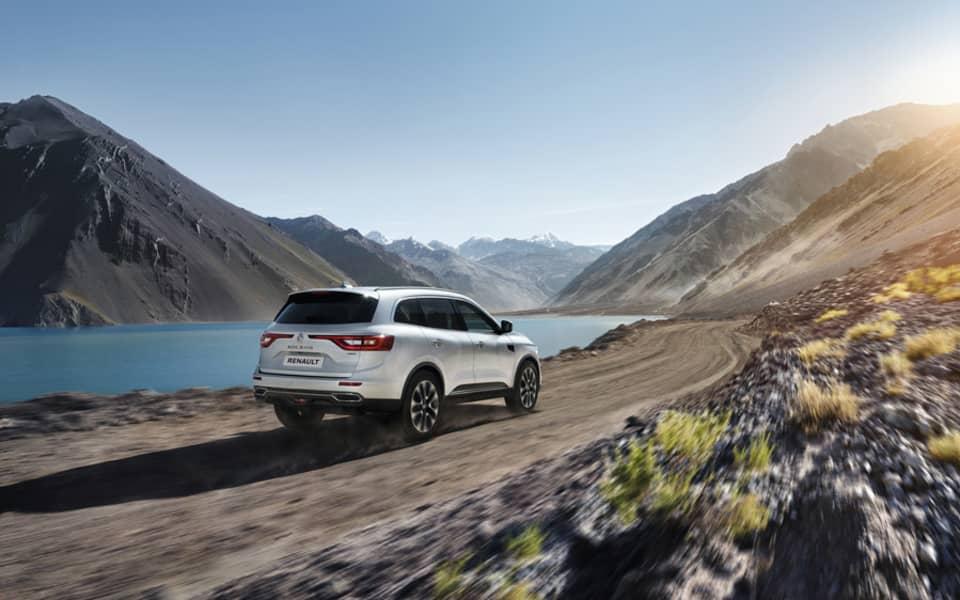 Sølvfarget Renault Koleos kjører langs fjorden på grusvei