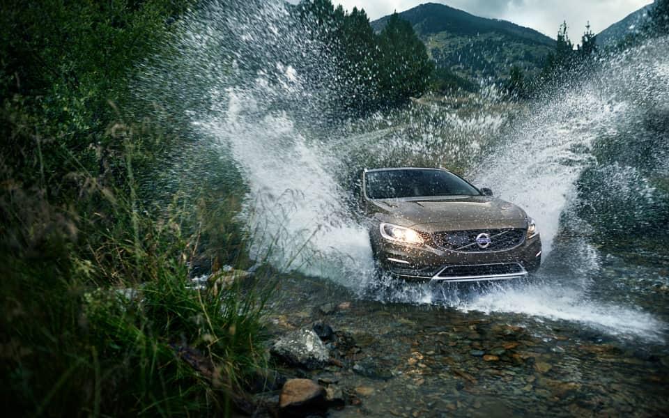Brun Volvo V60 Cross Country kjører gjennom elveleie og spruter vann
