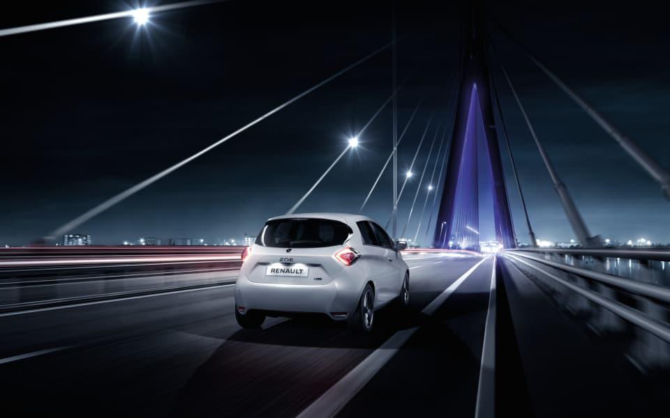En hvit Renault Zoe kjører mot en storby i nattemørket.