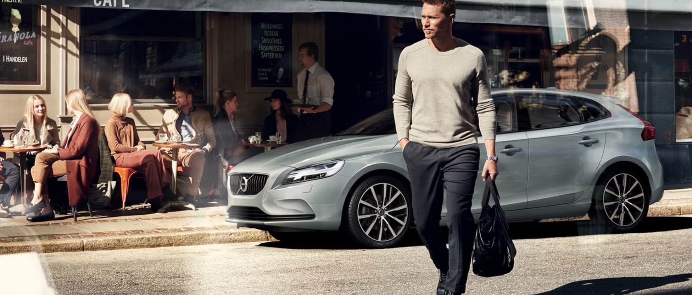 Volvo V40 Momentum parkert foran cafe mann med veske går mot kamera
