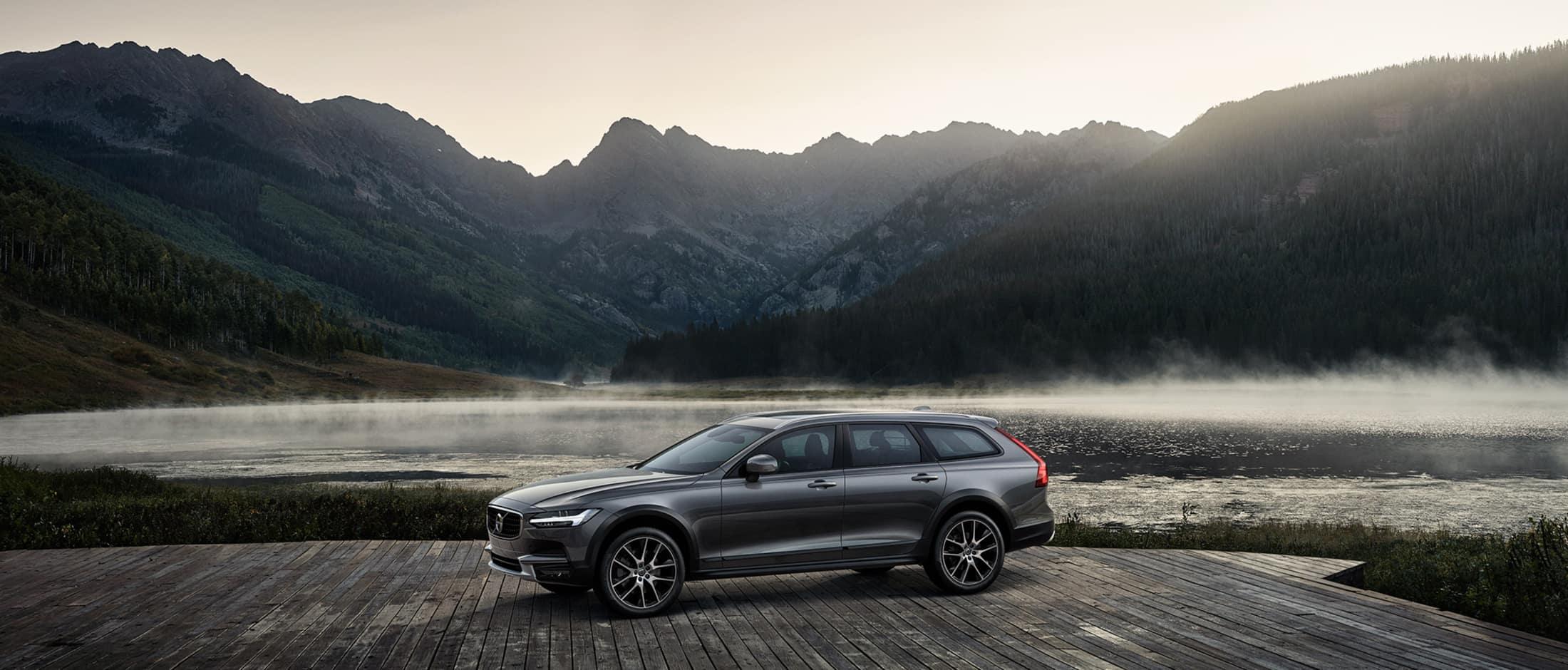 Volvo V90 Cross Country parkert på platting foran fjord i tåketeppe