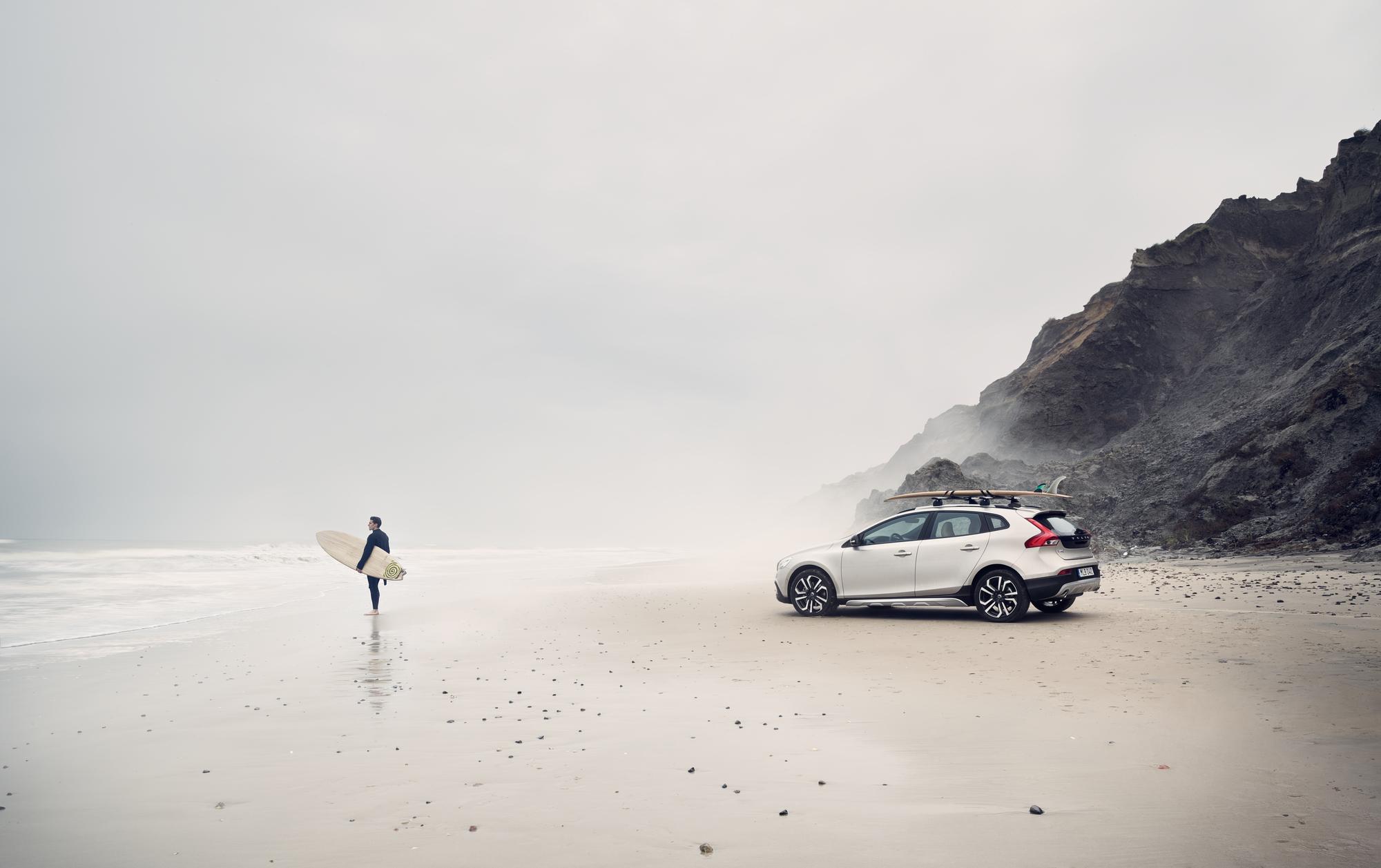 Surfer beskuer vannet på stranden foran en hvit Volvo V40 Cross Country