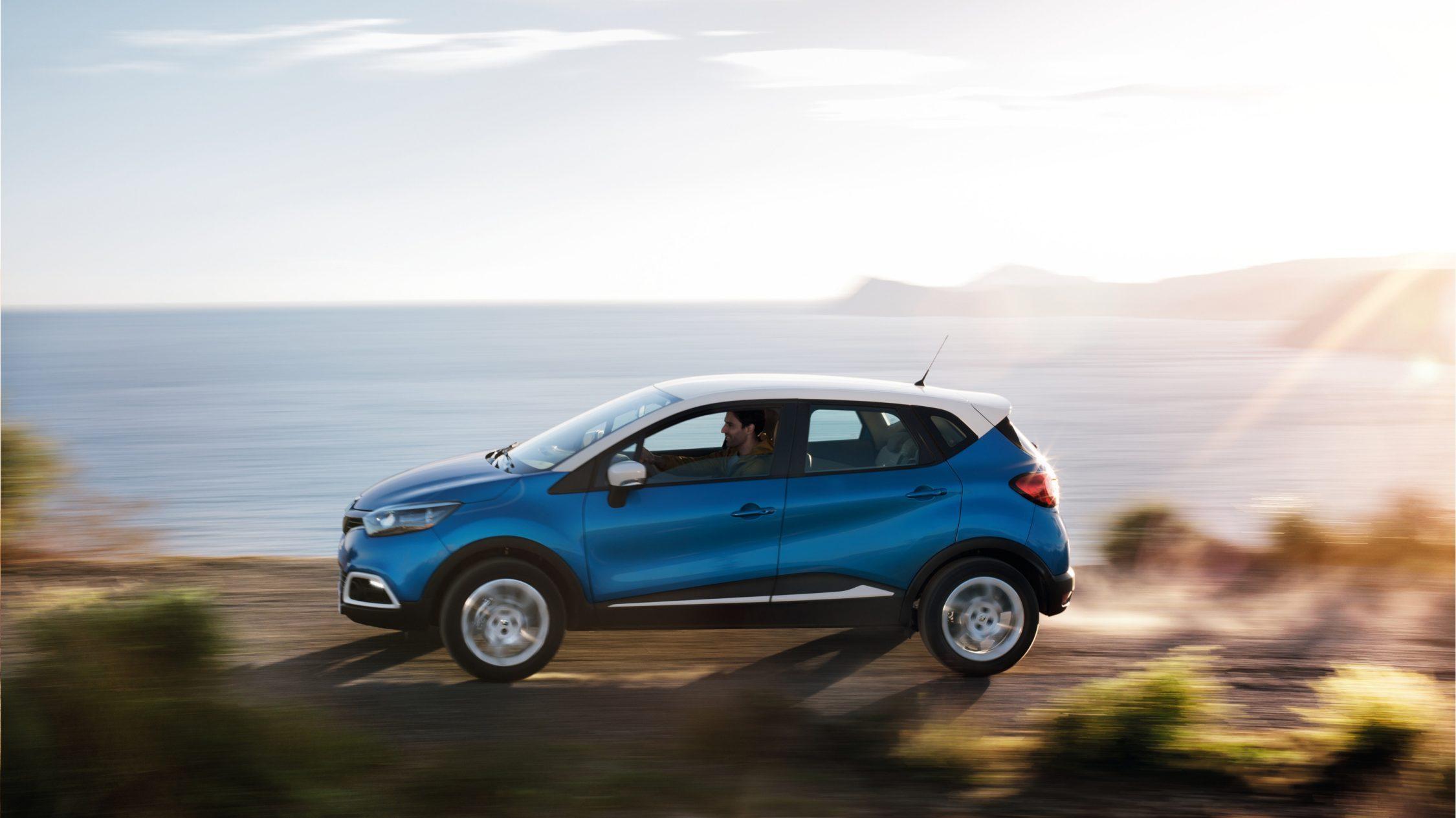 Blå Renault Captur kjører langs kysten
