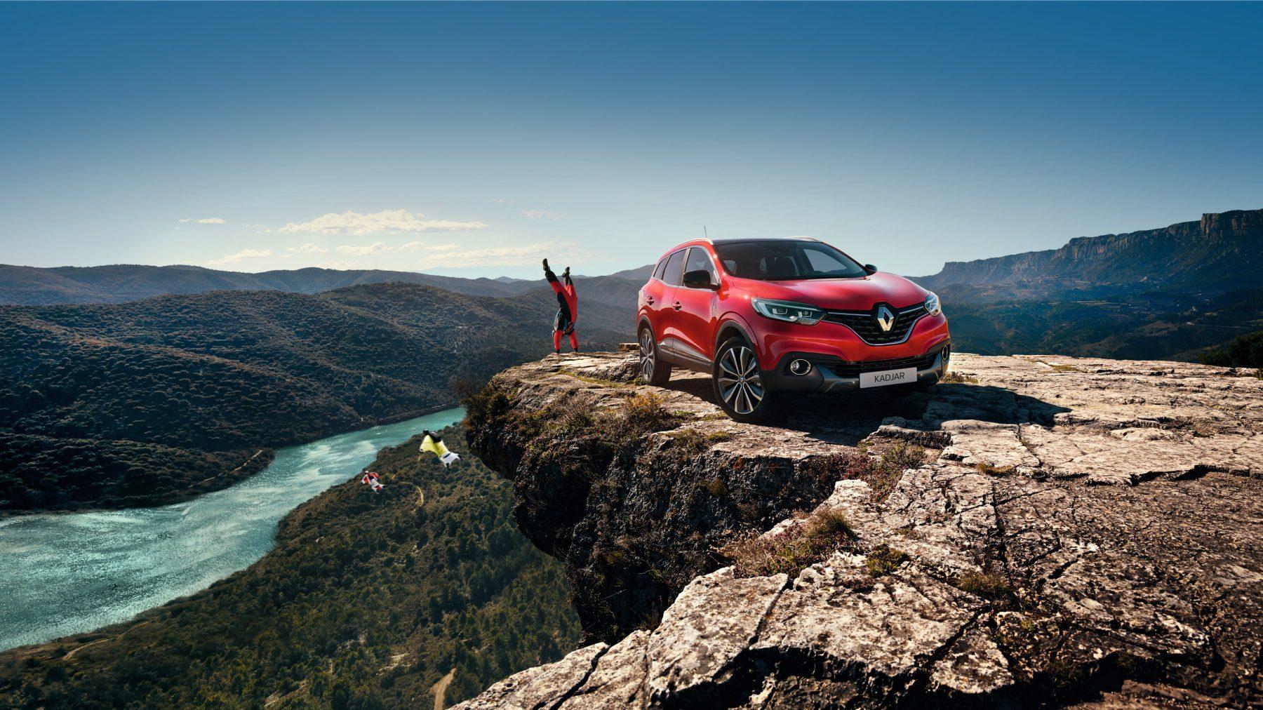 Rød Renault Kadjar parkert på toppen av et fjell med basehopper i bakgrunnen
