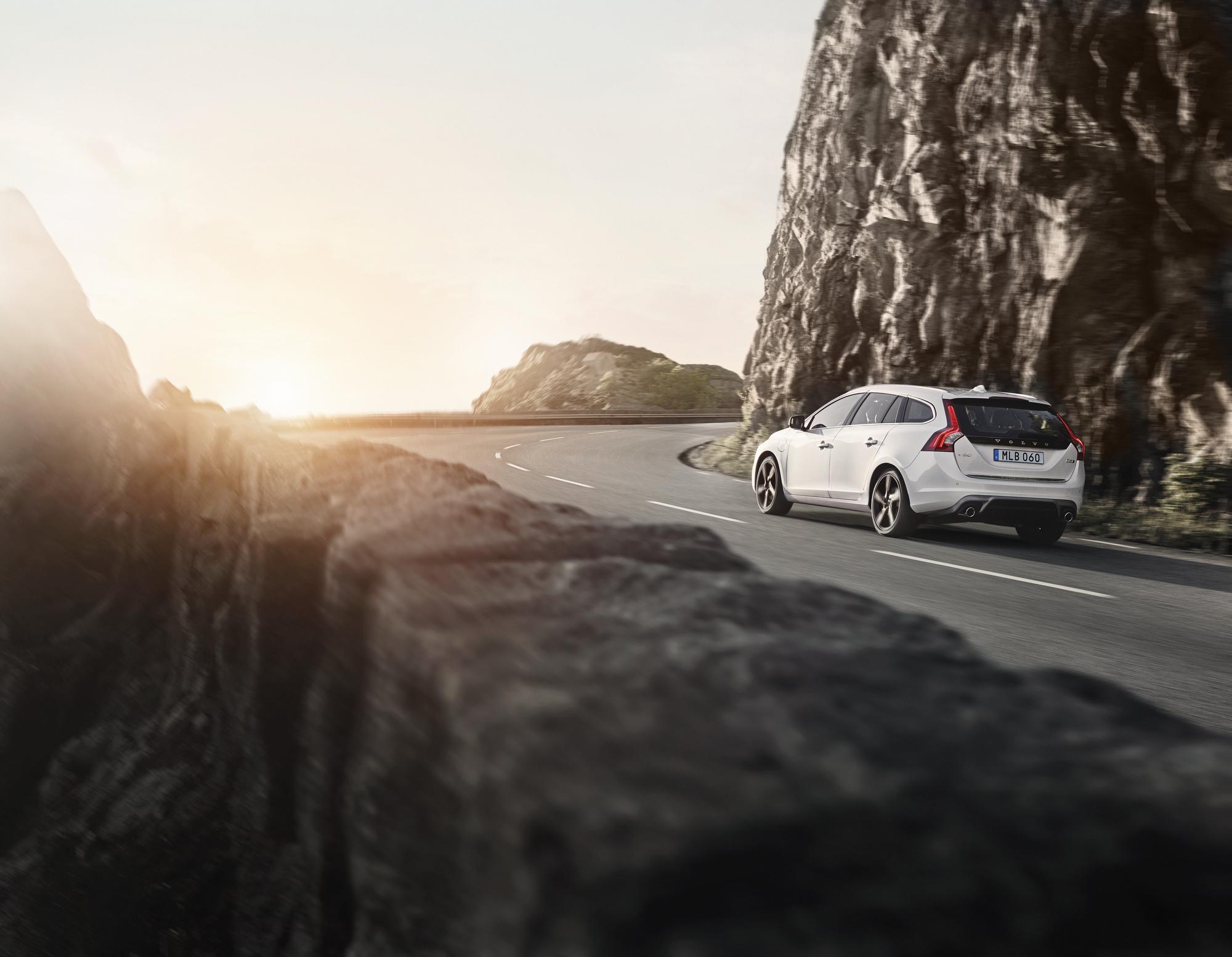 Volvo V60 Twin Engine Plug-in Hybrid kjører fra oss på en fjellvei i solen