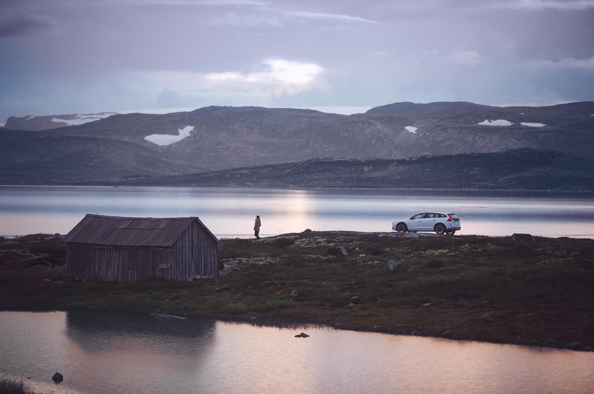 Hvit Volvo V60 Cross Coontry parkert på en odde med et gammelt naust
