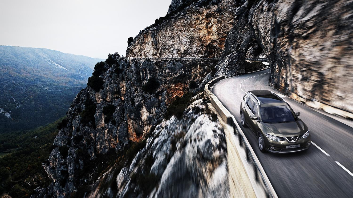Nissan X-Trail i vakkert landskap på svingete vei