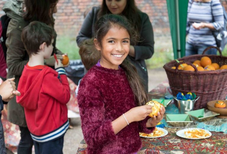 A girl smiles as she puts cloves into an orange