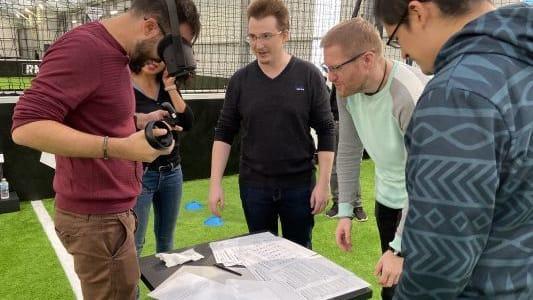 groupe de personnes qui regardent un homme équipé d'un casque VR