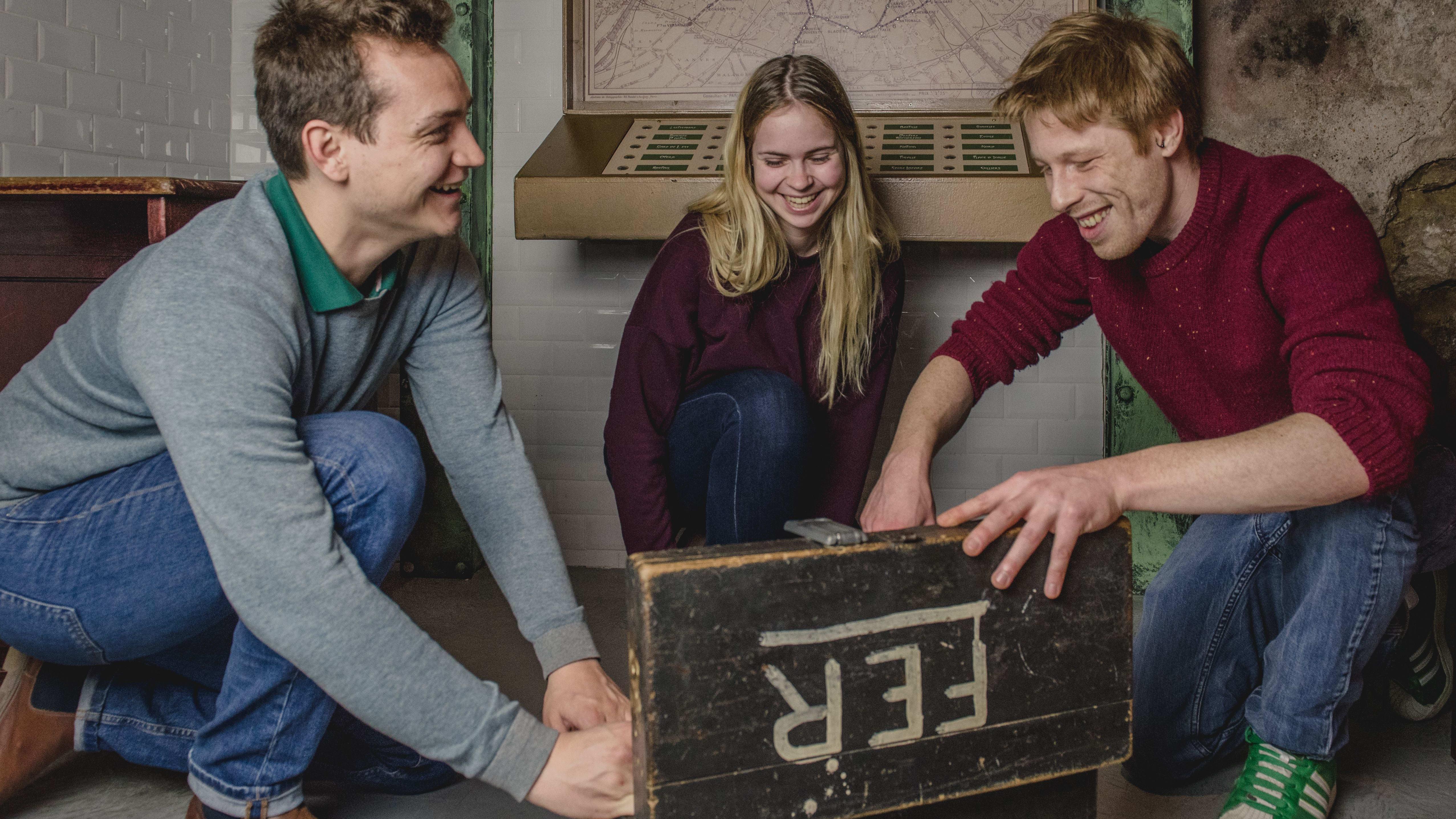 Trois salariés ouvrant un coffre dans une salle d'escape game