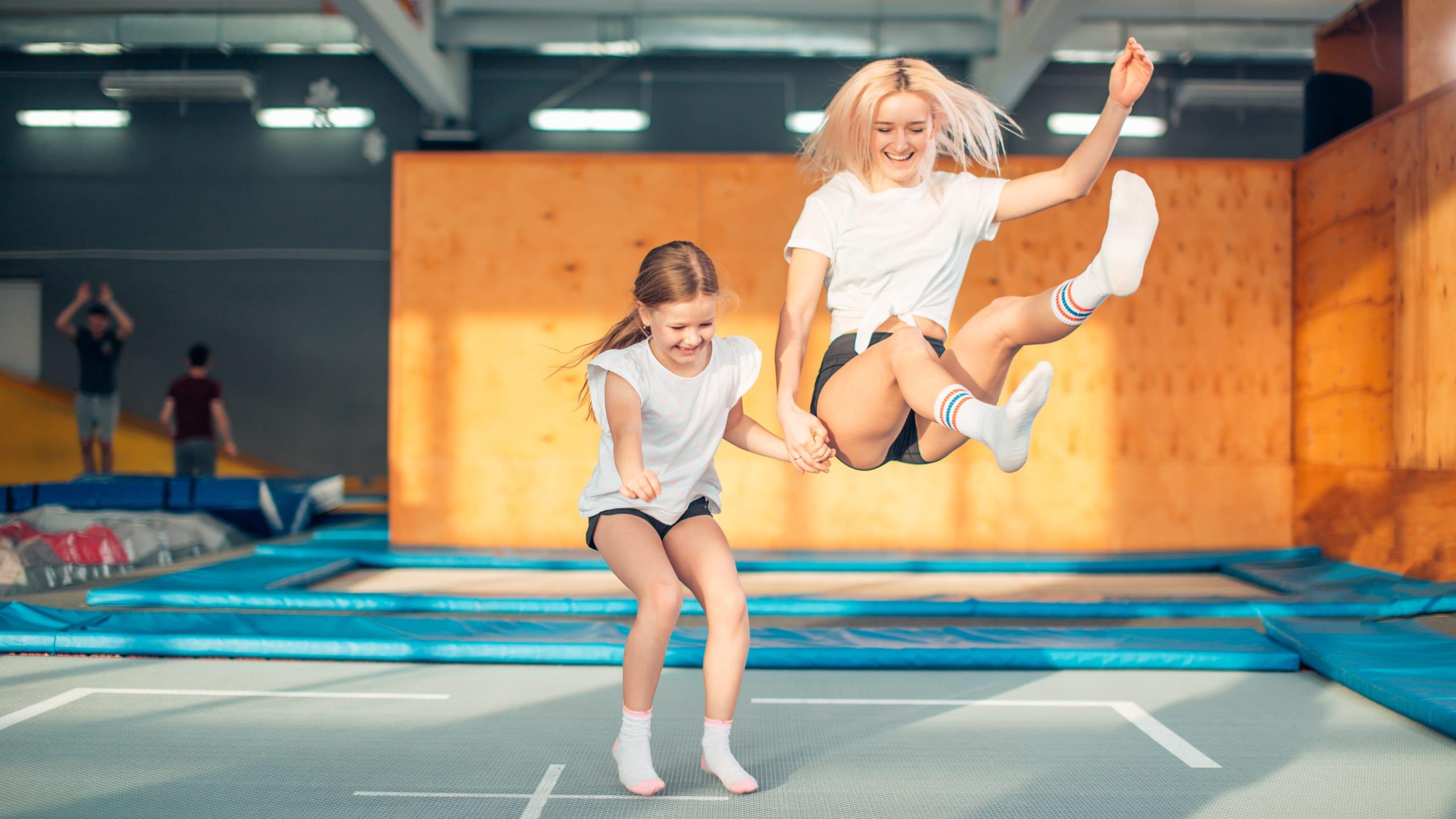 deux filles souriantes sautant en trampoline