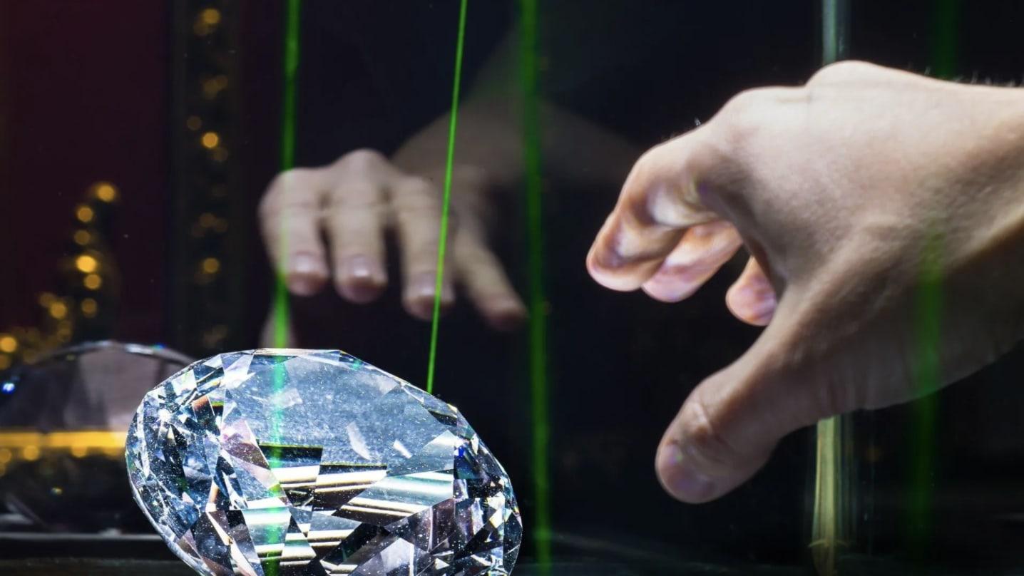 main tentant de récupérer un diamant protégé par des détecteurs laser