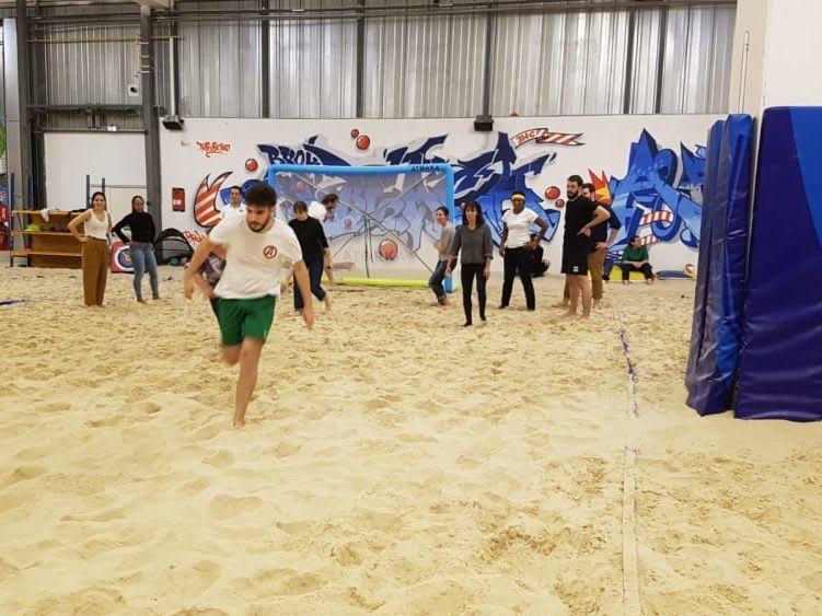 Salariés d'amusant dans un hangar, sur un terrain de Beach Soccer