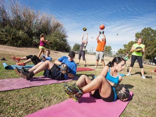 Salarié faisant du sport dehors sur un tapis de fitness et avec des medicine balls
