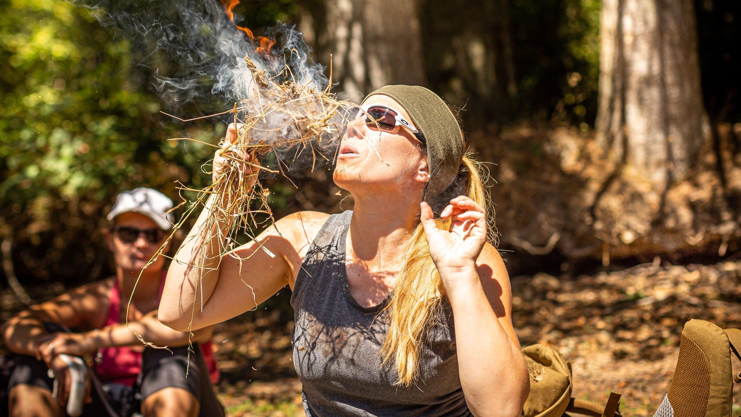 Femme qui essaye de faire du feu