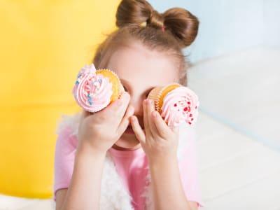 petite fille qui cache ses yeux avec deux cupcakes