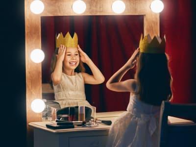 Petite fille avec une couronne se regardant dans le miroir d'une loge