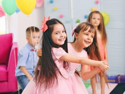 Deux petites filles souriantes qui dansent en se tenant la main