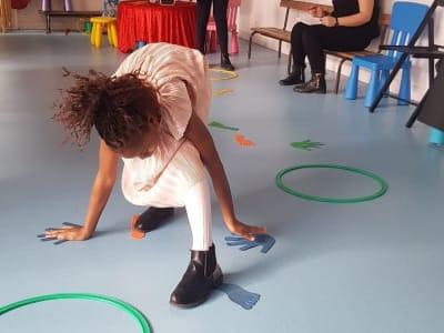 Fille jouant avec des stickers au sol