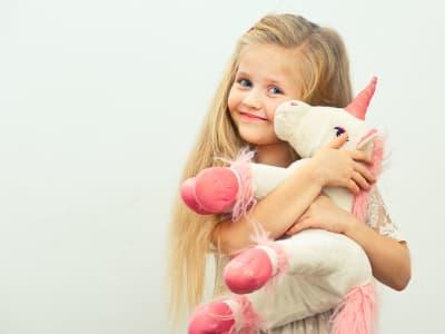 petite fille qui fait un calin à une licorne en peluche
