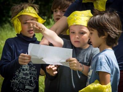 enfants avec bandana jaune lisant une carte pour une chasse au trésor