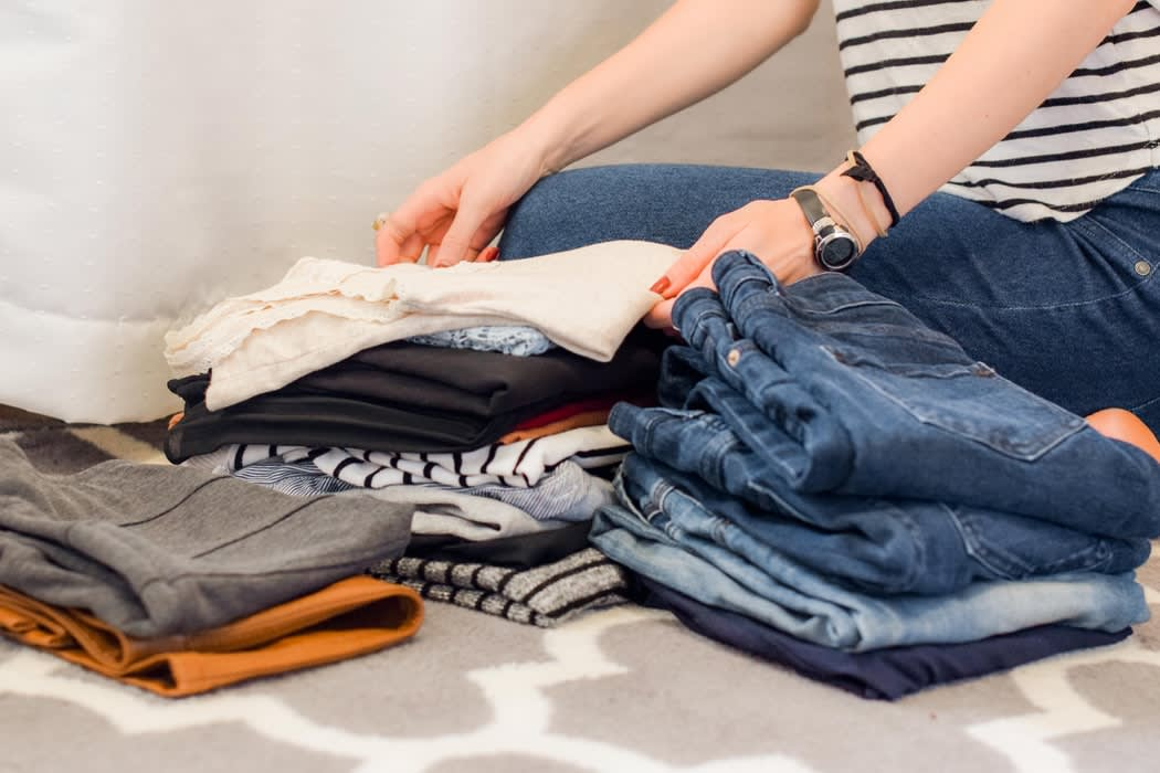 A woman organizing piles of clothes, representing the act of Swedish Death Cleaning and funeral comparison services from Funeralocity