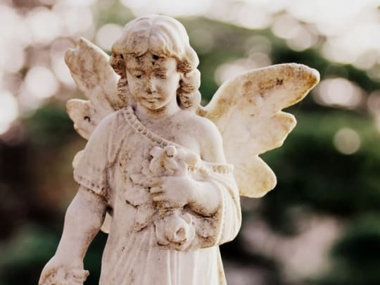 An angel carved out of stone on a grave, symbolizing the cremation services offered by funeral homes on Funeralocity, a comparison website