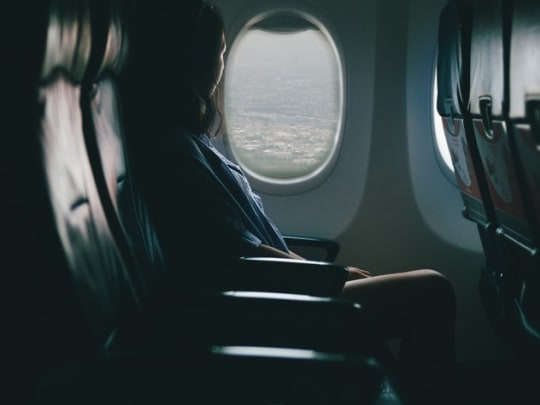 A person sitting in the window seat of an airplane