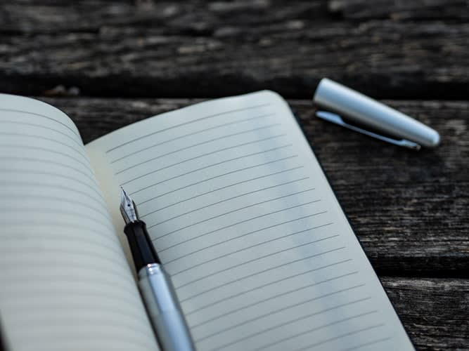 A fountain pen and notebook representing funeral pre-planning by Funeralocity