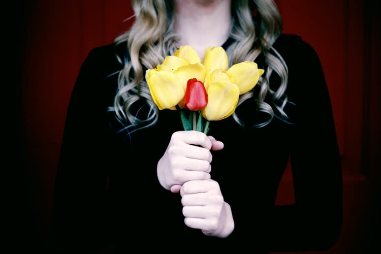 Woman holding a bouquet of yellow flowers and one red flower