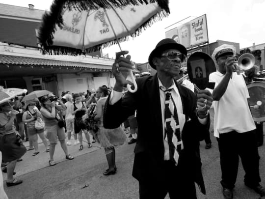 A man in a black suit holds a parasol in a second line, highlighting the funeral comparison services of Funeralocity