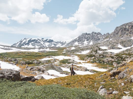 A woman hiking in the Rocky Mountains to scatter the ashes of a loved one after using Funeralocity to find a funeral home to perform the cremation