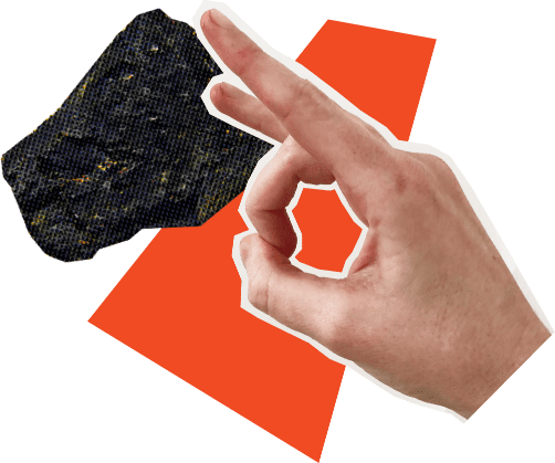 A hand flicking a piece of coal