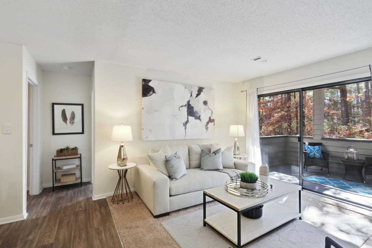 Model home's well-furnished living space next to the private balcony outside at Reserve at Peachtree Corners in Norcross, Georgia