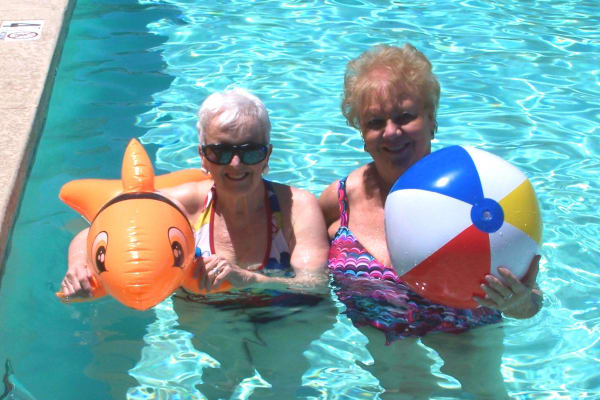 Two residents in the pool at The Palms at LaQuinta Gracious Retirement Living in La Quinta, California