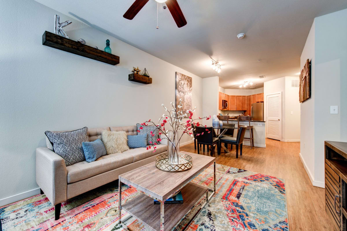 Spacious living room with a large rug covering wood floors at The Marq on West 7th in Fort Worth, Texas