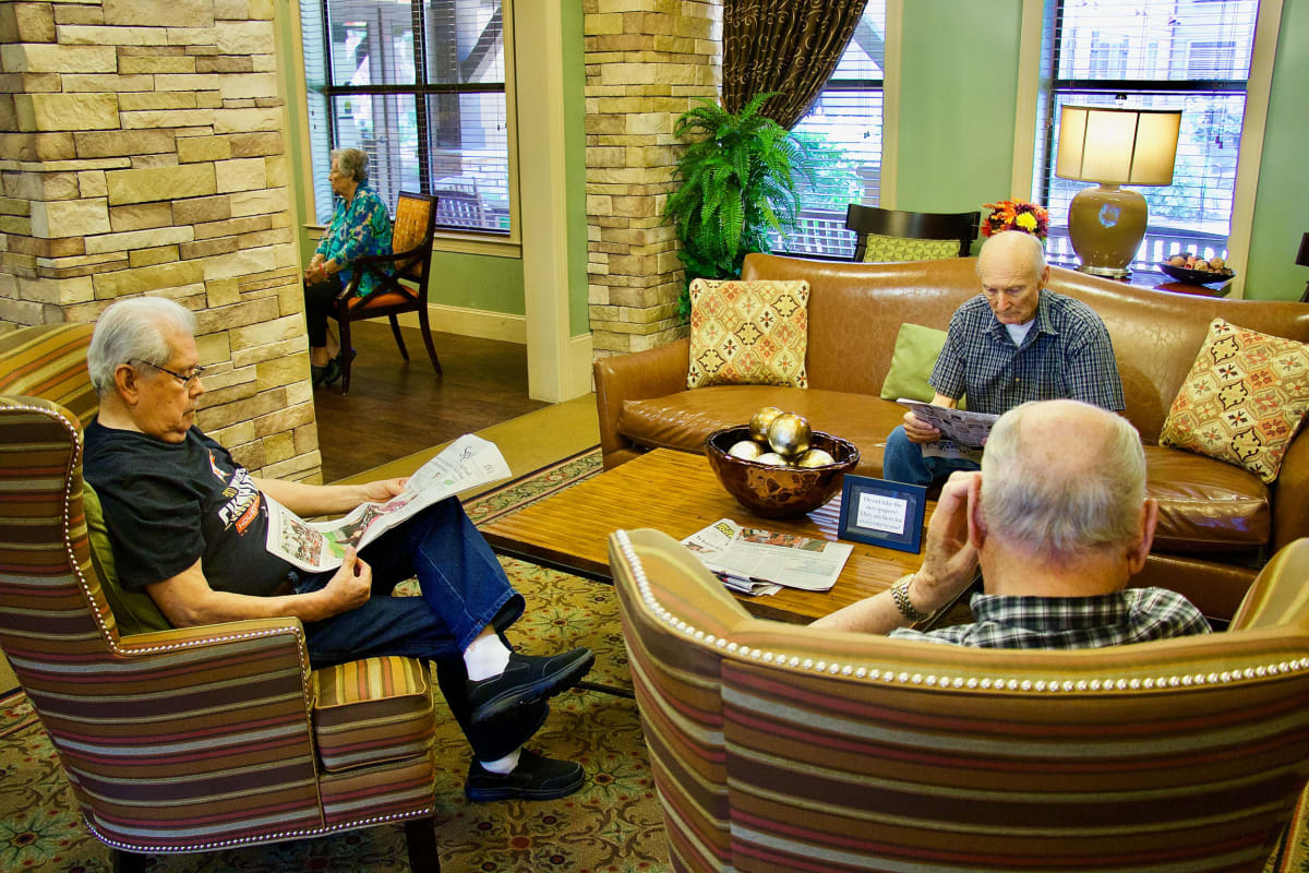 A few residents enjoying their morning by reading at Isle at Watercrest Bryan in Bryan, Texas