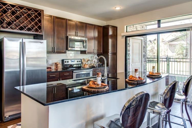 Modern kitchen with stainless-steel appliances in a model home at Waterford Trails in Spring, Texas