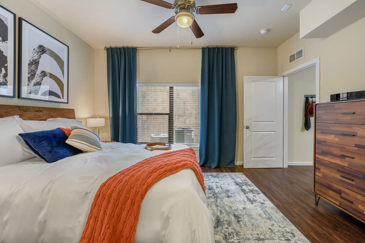 Bright bedroom with wood style flooring at Marquis SoCo in Austin, Texas