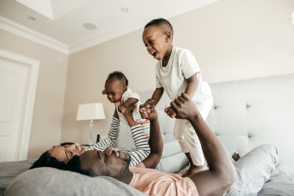 Happy family playing in the bedroom at Avilla Grace in Chandler, Arizona