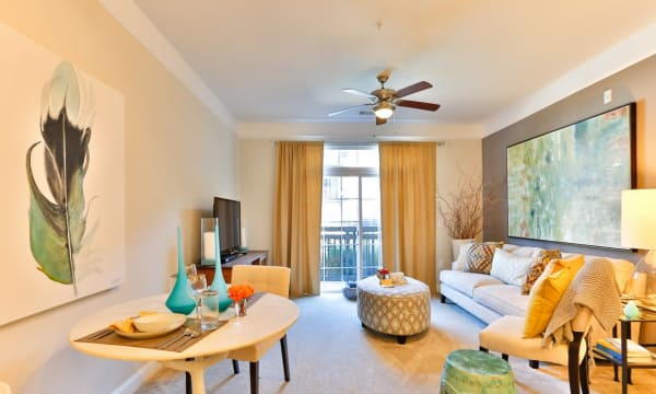 Living room with carpet and ceiling fans at Fountains at Mooresville Town Square in Mooresville, North Carolina