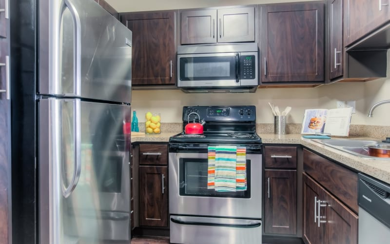 Renovated kitchen with stainless steel appliances at Tuscany Village Apartments in Ontario, California