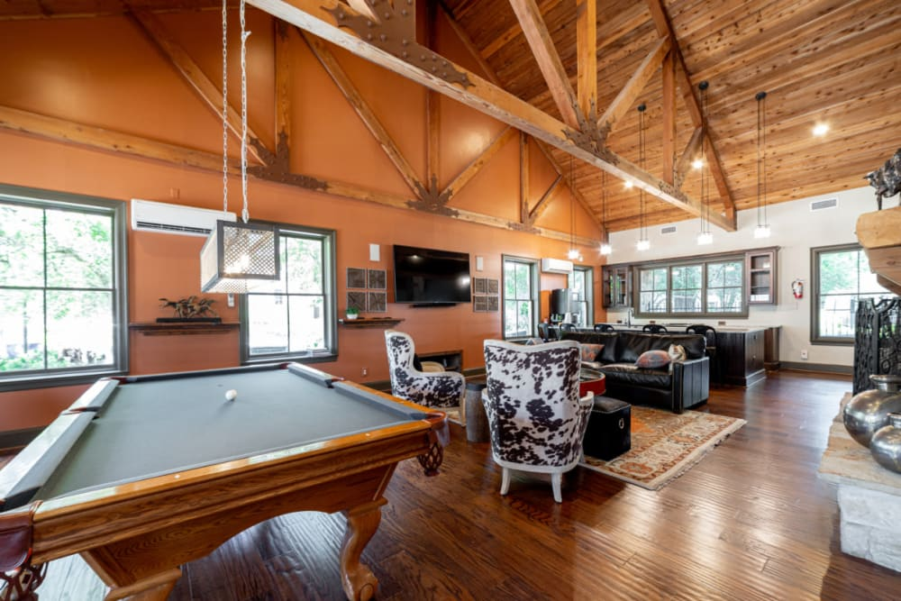 Pool table, seating area, and kitchen in rustic clubhouse at Marquis at Bellaire Ranch in Fort Worth, Texas
