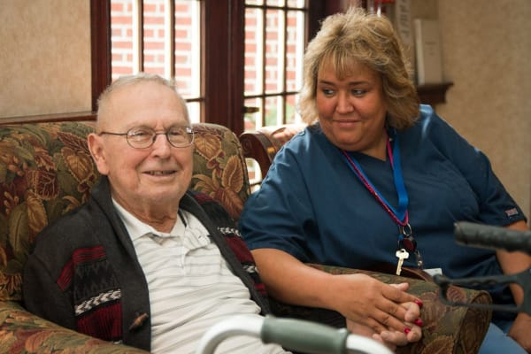 Resident sitting with a caretaker smiling at Governor's Pointe in Mentor, Ohio