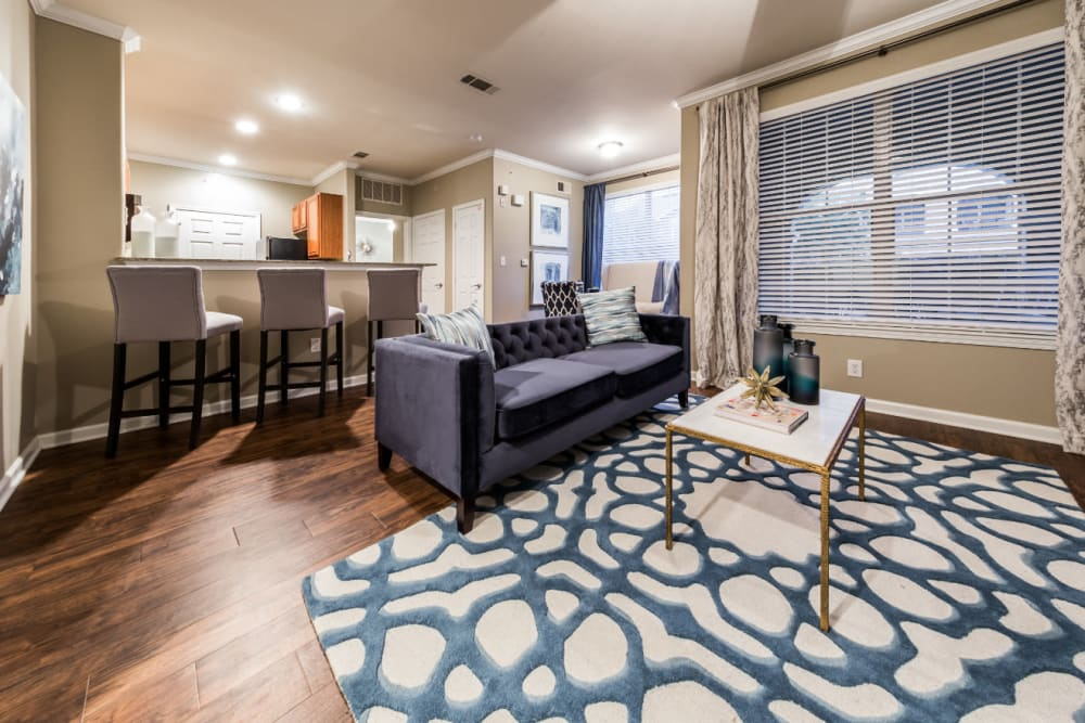 Modern style living room with large window and wood flooring at Marquis at The Cascades in Tyler, Texas