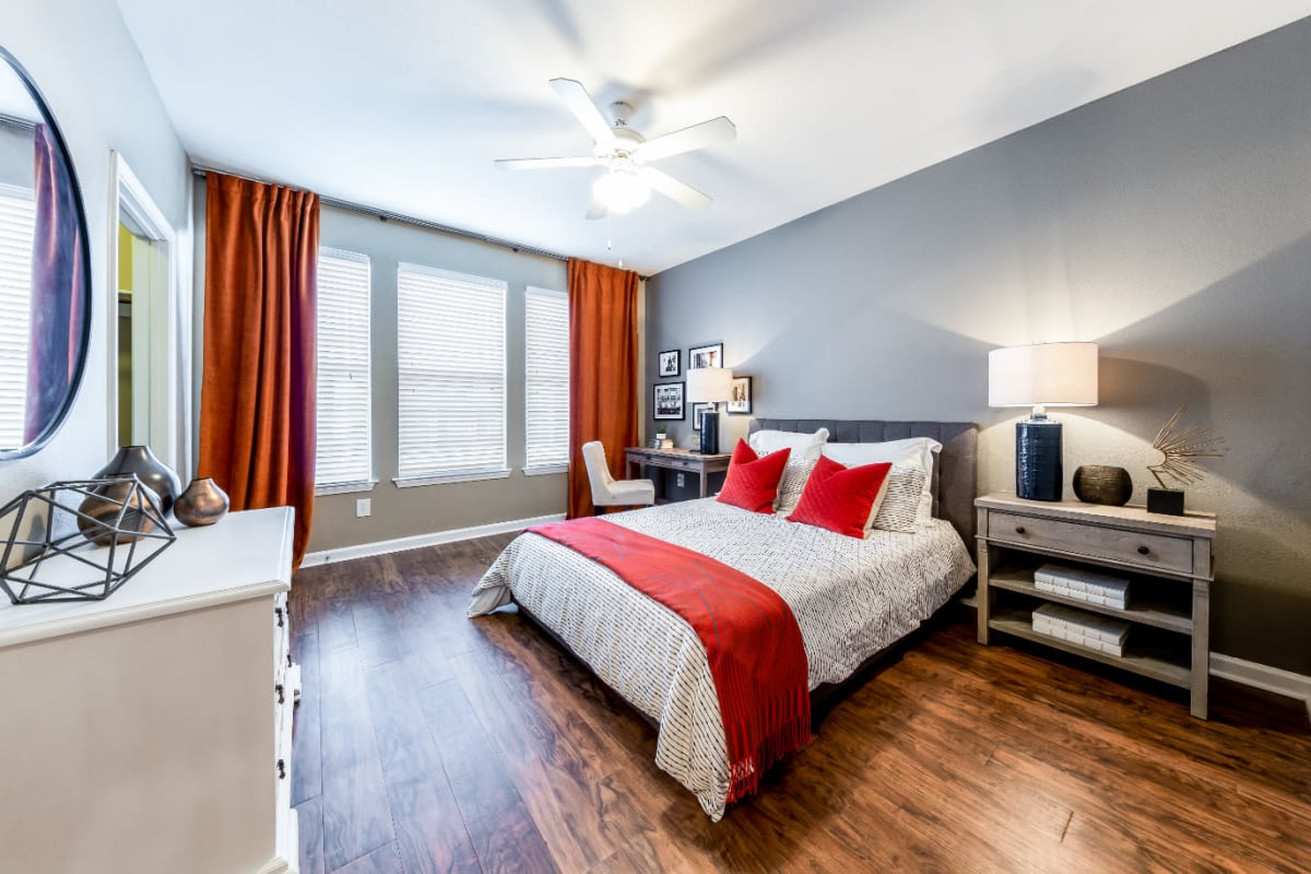 Bright and cheerful bedroom with wood flooring, multiple windows, and walk-in closet at Marquis at Stone Oak in San Antonio, Texas