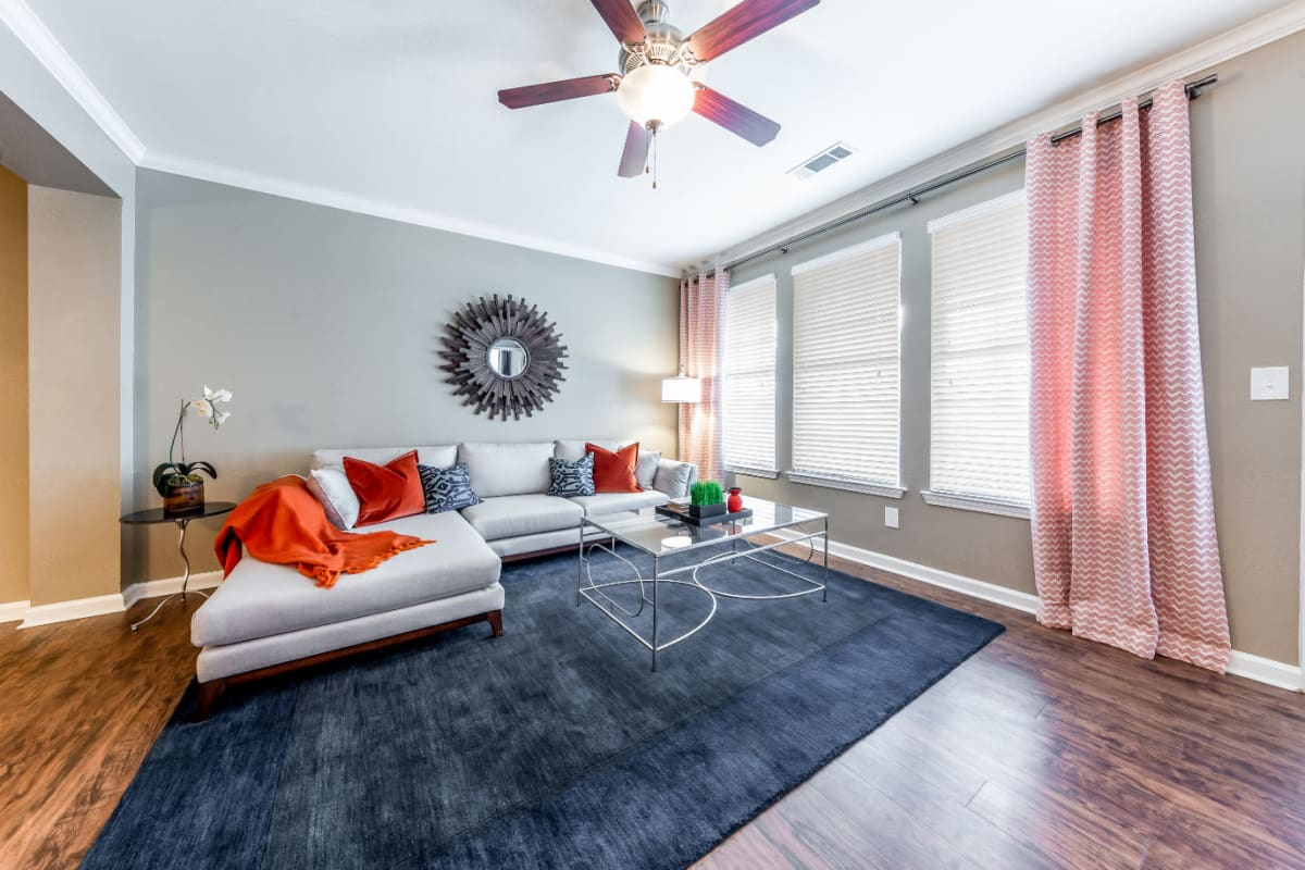 Bright living area with multiple windows and wood flooring at Marquis at Stone Oak in San Antonio, Texas