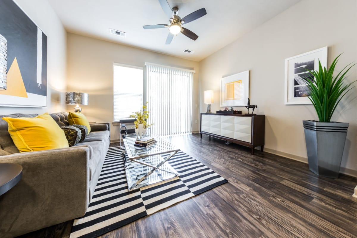 Bright and modern style living room with wood flooring and access to balcony at Marq Uptown in Austin, Texas
